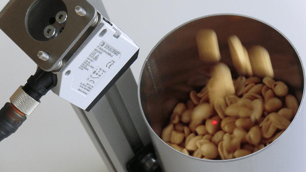 Niveaumeting van pinda's in een container bij het afvullen van zakjes - SensoPart